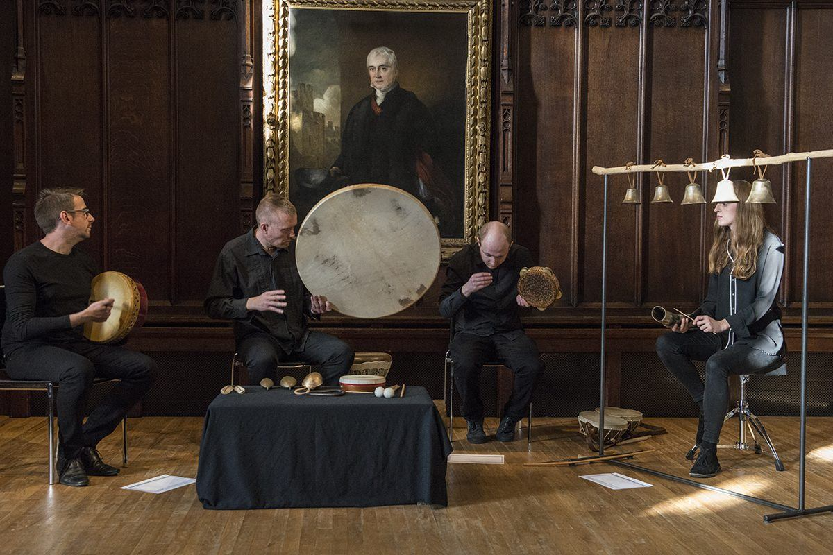 Four musicians playing instruments in an old, wood panelled room.